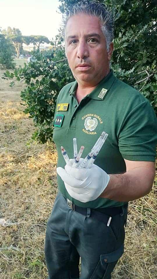 Un volontario Nogra che raccoglie le siringhe dal marciapiede di Ladispoli